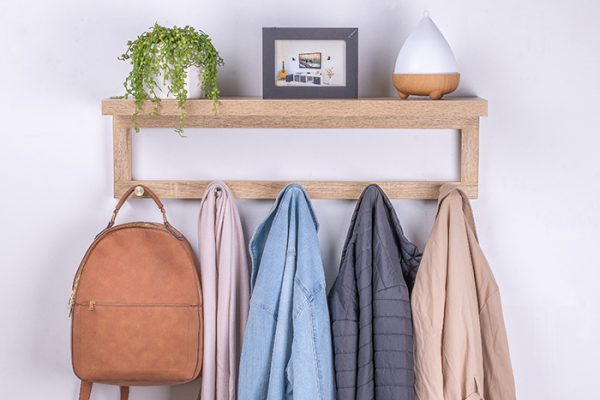 Flexi Storage Decorative Shelving Coat Shelf With Hooks Oak installed on wall with decorations on shlef and coats and bag hanging on hooks